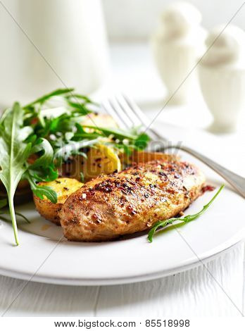 Spiced chicken breast with baked potatoes  and arugula