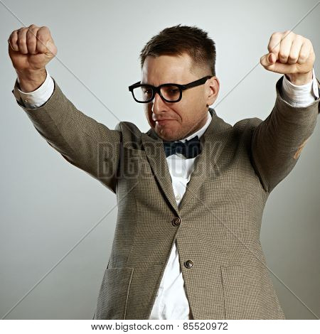 Confident nerd in eyeglasses and bow tie enjoying success against grey background
