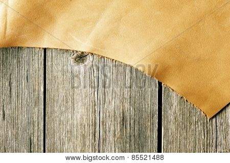 Piece of leather over wooden background