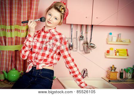 Pretty pin-up girl teenager smarten up on a pink kitchen. Beauty, youth fashion. Pin-up style.