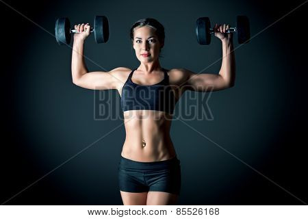 Slender young woman with beautiful athletic body doing exercises with dumbbells. Fitness, bodybuilding. Health care.