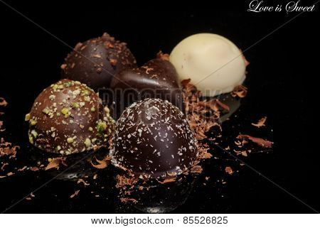 Low Key lighting on a selection of premium chocolates, on a reflective background and shallow DOF, with space for text