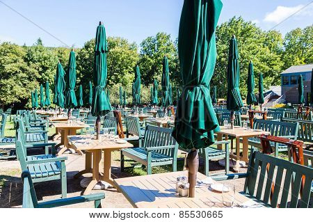 Outdoor Tables With Green Umbrellas And Chairs