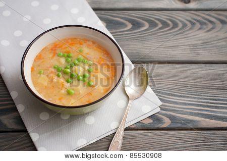 Split pea soup on wooden background.