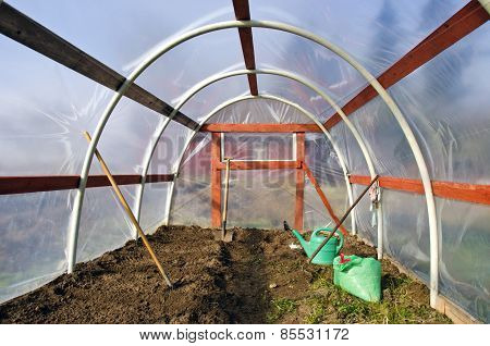 Early Spring Time Greenhouse Inside Construction With Gardener Tools