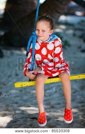 Adorable little girl having fun on swing on summer day