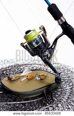 Fishing Rod And Reel With Bag For Baits On White.