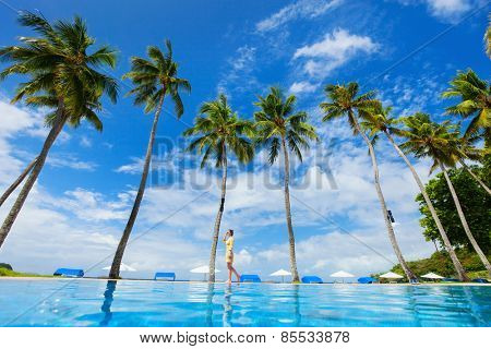 Young beautiful woman walking along infinity pool at tropical beach with palms