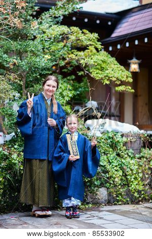 Family mother and daughter wearing traditional Japanese kimono at street of onsen resort town in Japan. Translation of text on wooden plate: passport for round bath visit to protect you from bad luck.