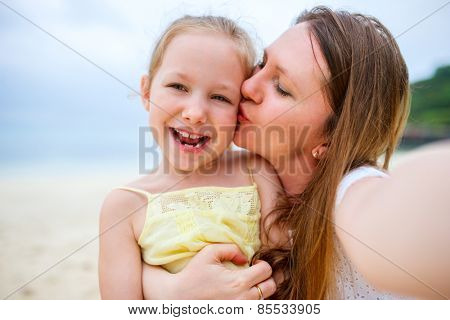 Happy family mother and her adorable little daughter at beach making selfie