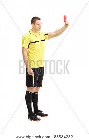 Full length portrait of a football referee showing a red card isolated on white background
