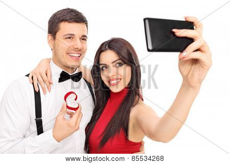 Young couple taking selfie with their engagement ring isolated on white background