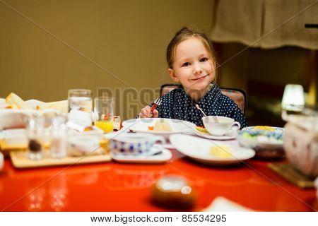 Adorable little girl wearing traditional yukata kimono eating Japanese breakfast