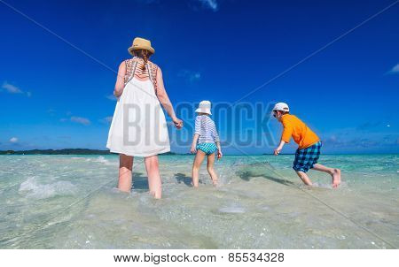 Back view of mother and two kids walking on shallow water at tropical beach enjoying summer vacation