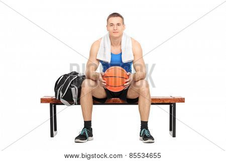 Male basketball player sitting on a bench isolated on white background