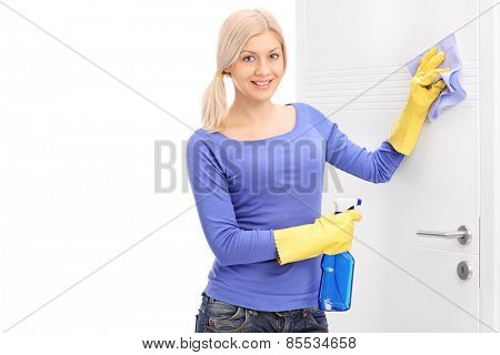 Woman cleaning a door with rag isolated on white background