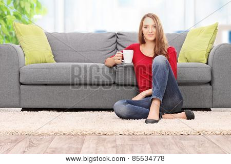 Young woman drinking coffee seated by a sofa at home