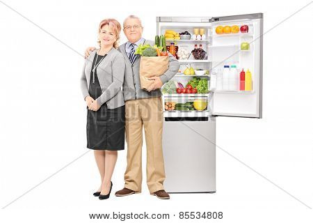 Mature couple holding groceries in front of a fridge isolated on white background