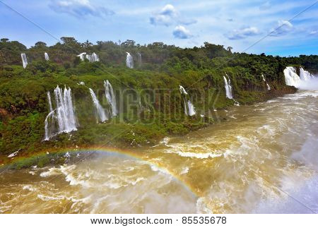 Raging and roaring water in the waterfalls of Iguazu. Turbid yellow-brown waves flow down. Above the water is a picturesque rainbow