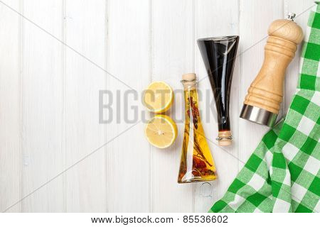Condiments and spices over white wooden table with copy space