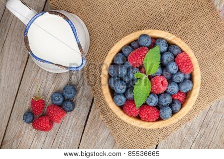Blueberries and raspberries bowl and milk jug on wooden table