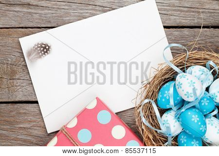 Easter greeting card with blue and white eggs and gift box over wood. Top view with copy space