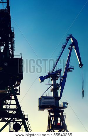 Cranes At The Port For Loading On A Background Of The Sun And Sky