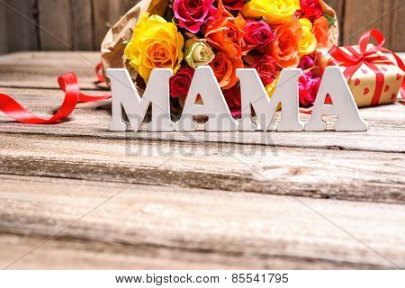 Bunch of roses with a gift box and word Mama on wooden background