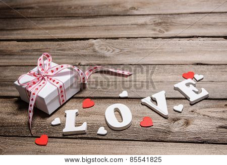 Gift box with word LOVE on wooden background