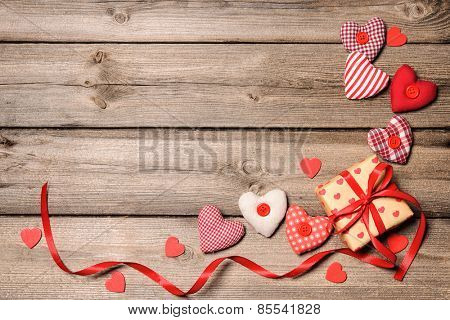 Gift box with red ribbon with textile hearts on wooden background