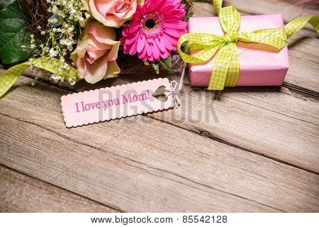Bunch of flowers and tag with text on wooden background. I love you Mom