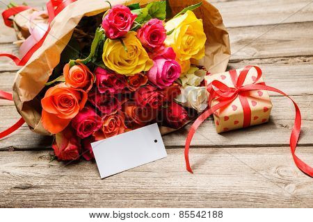 Bunch of roses and gift box with an empty tag on wooden background