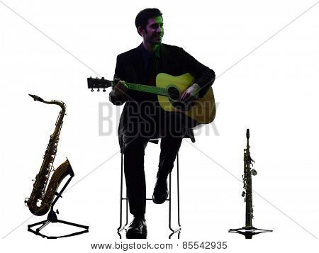 one caucasian man acoustic guitarist player playing in studio silhouette isolated on white background