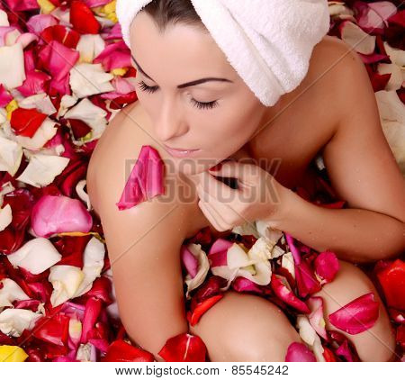 Beautiful female in bath with rose petal. Body care.