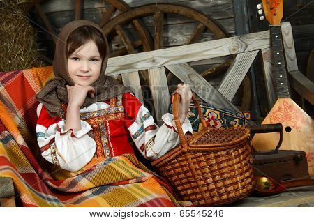 Beautiful girl in russian costume sitting in a traditional interior