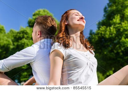 Couple in love sitting on park lawn enjoying sun