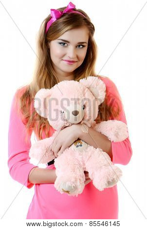 beautiful smiling girl in pink a dress with a teddy bear
