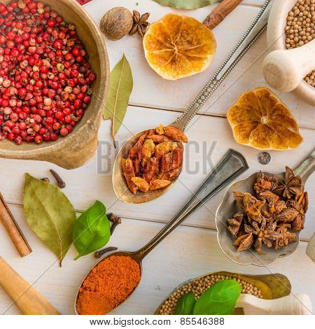 spoons with herbs and spices on white wooden background