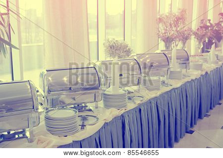 Table with dishware and shiny marmites waiting for guests, toned image