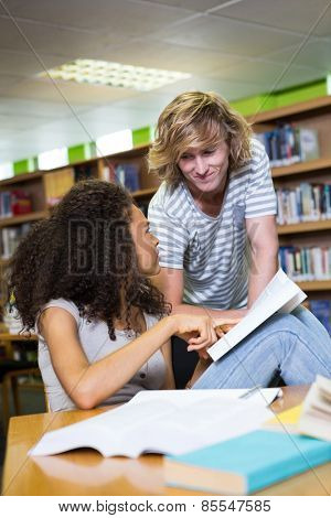 Student getting help from classmate in library at the university