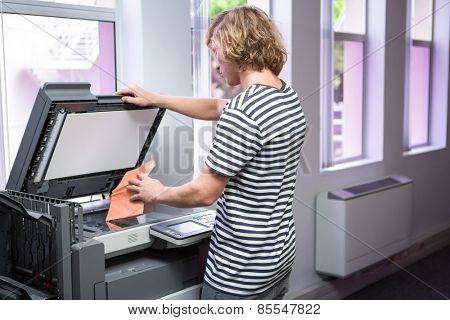 Student photocopying his book in the library at the university