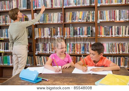 Teacher looking for a book at library at elementary school