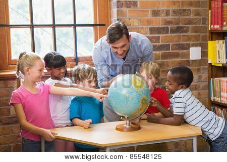 Cute pupils and teacher looking at globe in library at elementary school