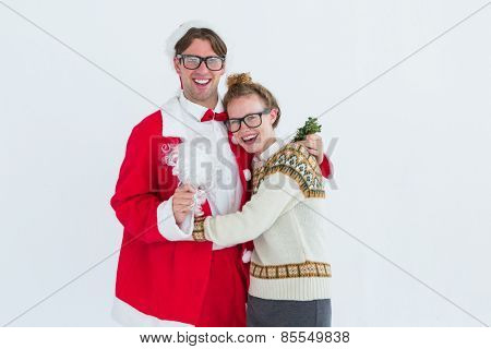 Geeky hipster in santa costume hugging his girlfriend on white background