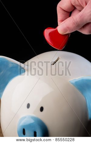 Hand putting heart in piggy bank shot in studio