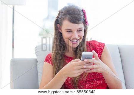 Pretty hipster using her smartphone on the couch