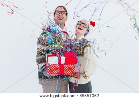 Excited geeky hipster couple looking at confetti on white background