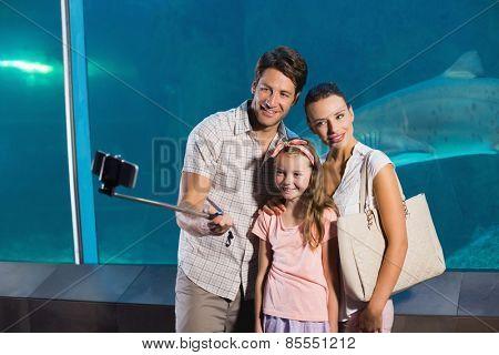 Happy family using selfie stick at the aquarium