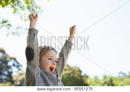 Cute little boy cheering in park on a sunny day