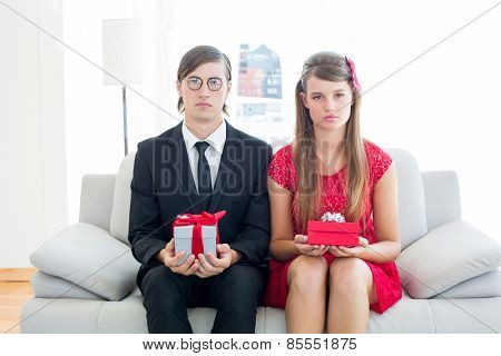 Unsmiling geeky couple with gift on the couch